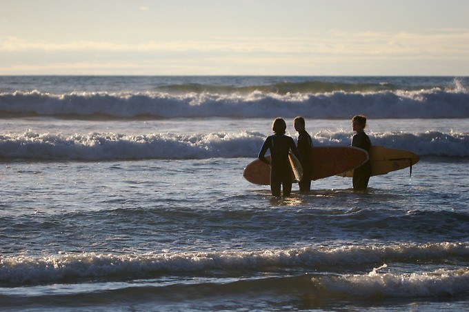 Tyler, Shelley, and Caeley head out to surf at sunset
